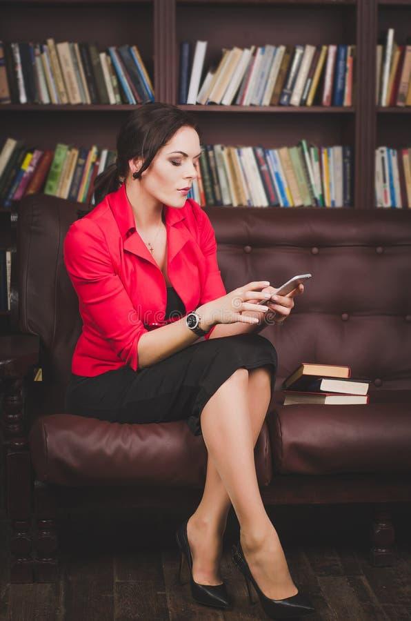 La mujer de negocios atractiva en oficina viste sentarse en un cuero imágenes de archivo libres de regalías