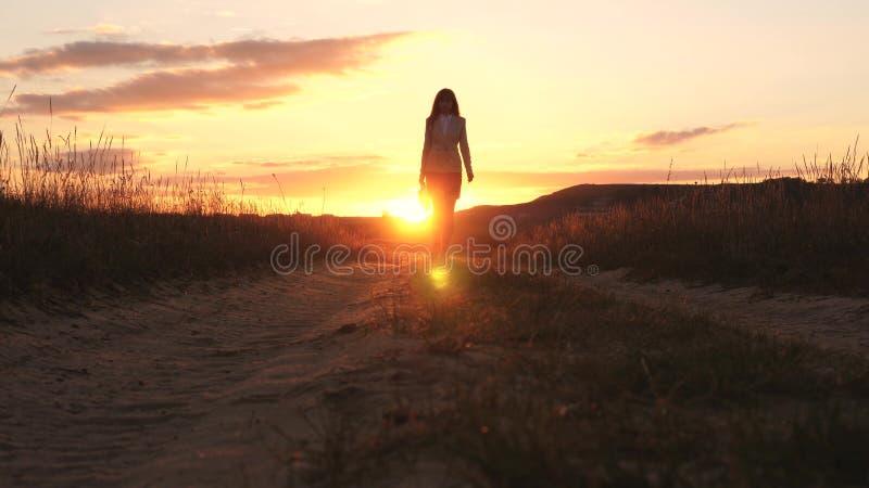 La mujer de negocios atractiva que camina a lo largo de una carretera nacional con una cartera a disposición, el sol riela en la  imagen de archivo libre de regalías