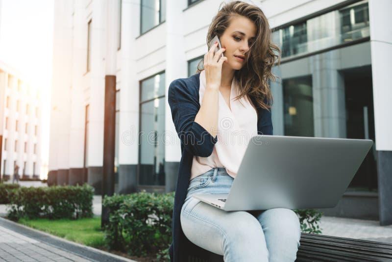 La mujer de negocios bonita joven se sienta en distrito financiero y la discusión sobre trabajo en la información del smartphone  foto de archivo