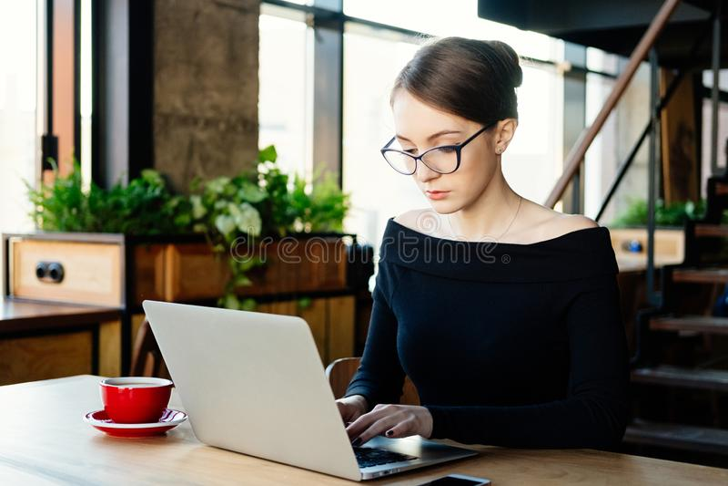 La mujer de negocios bonita joven trabaja en un ordenador portátil, aplicaciones un smartphone, freelancer, un ordenador, analist fotos de archivo