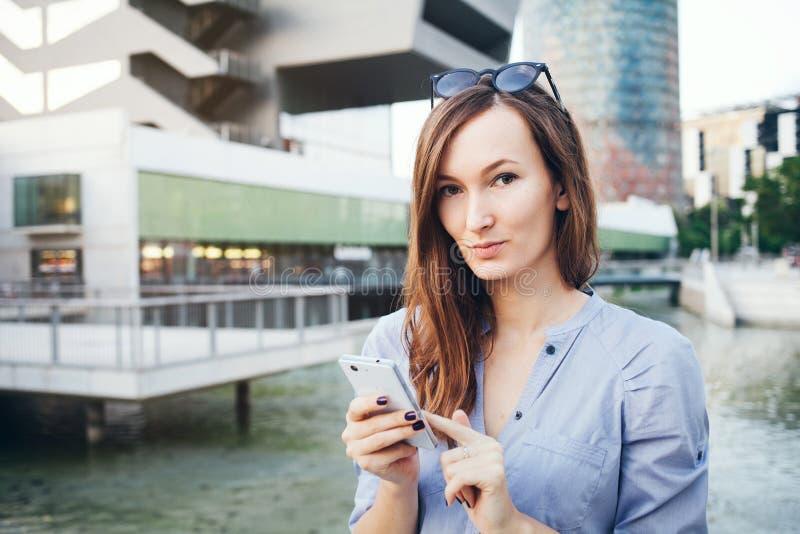La mujer de negocios caucásica bien vestida sonriente joven utiliza el Smart-teléfono foto de archivo
