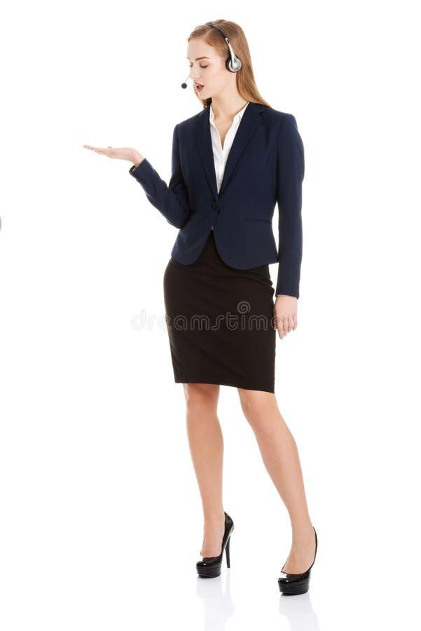 La mujer de negocios causual hermosa en el centro de atención telefónica está señalando en c fotografía de archivo