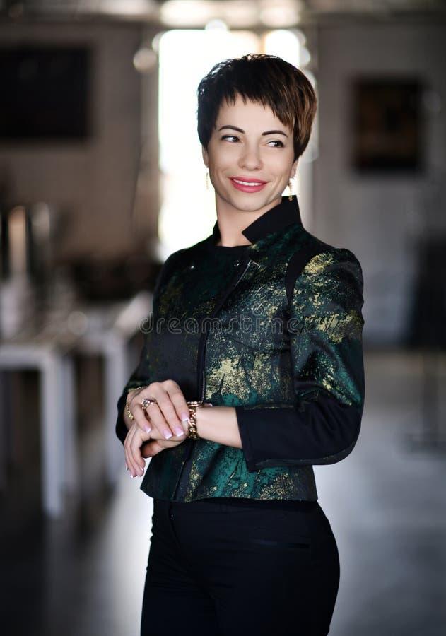 La mujer de negocios con el traje oficial de la moda adentro moderna encuentra alguien en oficina moderna imagen de archivo libre de regalías