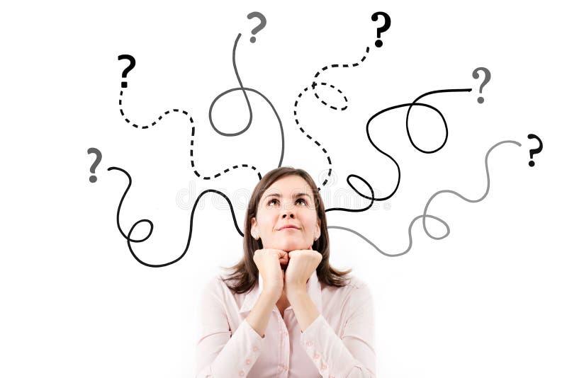La mujer de negocios con las flechas y las preguntas firman arriba aislado en el fondo blanco. imagenes de archivo