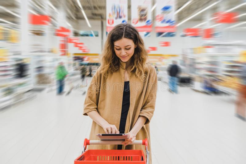 La mujer de negocios con la tableta se está colocando con el carro en el supermercado, la muchacha está eligiendo la comida y est fotos de archivo