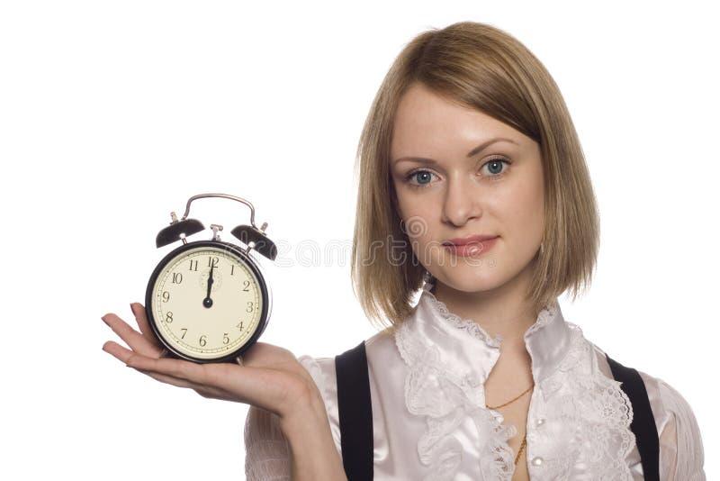la mujer de negocios con un reloj de alarma imagen de archivo