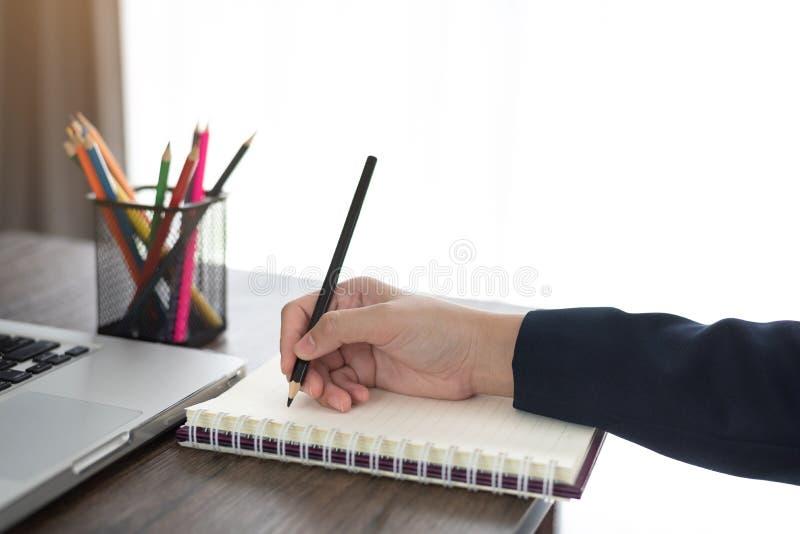 La mujer de negocios da la escritura o toma la nota sobre el libro en oficina imagenes de archivo