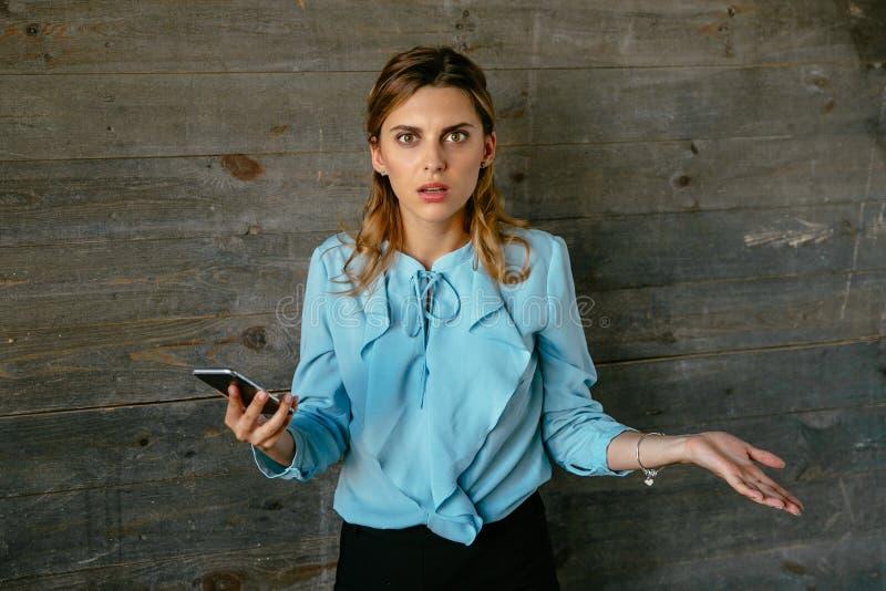 La mujer de negocios del trastorno parece confusa después de hablar en el teléfono móvil imagenes de archivo