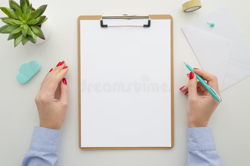 La mujer de negocios en camisa azul sostiene la pluma mofa del tablero para arriba con la tarjeta blanca del tamaño A4, aislada e fotos de archivo