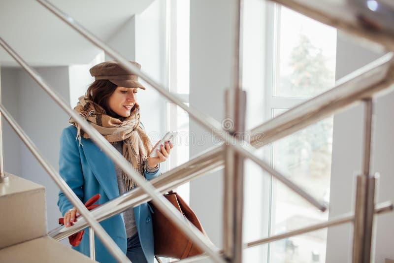 La mujer de negocios en capa sube las escaleras en la alameda Compras Moda imagenes de archivo