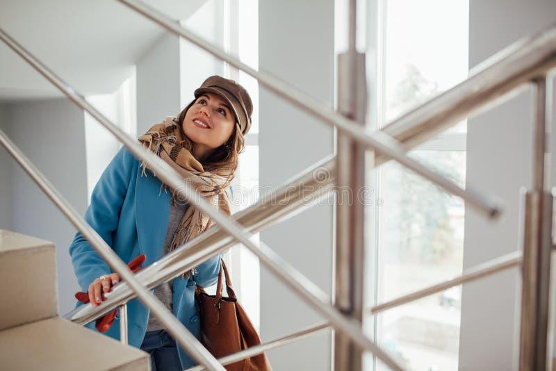 La mujer de negocios en capa sube las escaleras en la alameda Compras Moda foto de archivo libre de regalías