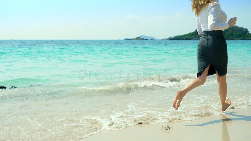 La mujer de negocios en ropa de la oficina corre descalzo al mar a lo largo de una playa arenosa blanca vacaciones independientes foto de archivo libre de regalías