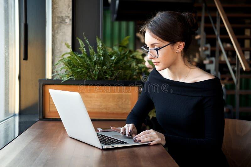 La mujer de negocios enfocada se sienta en el funcionamiento del café en el ordenador portátil fotos de archivo
