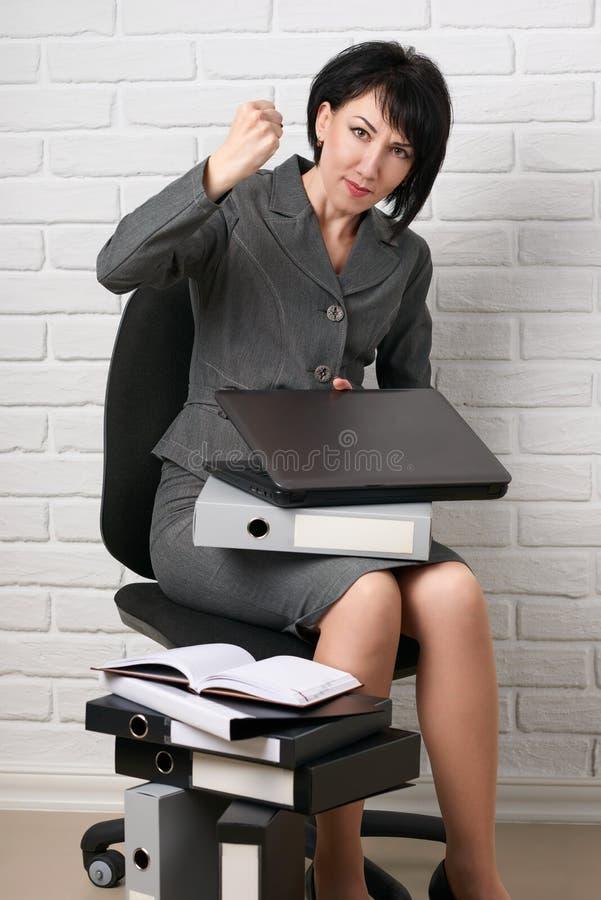 La mujer de negocios enojada con el ordenador portátil y las carpetas que hacen la tensión, vestir en un traje gris presenta dela foto de archivo libre de regalías