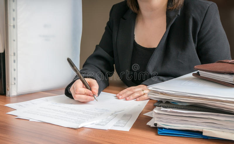 La mujer de negocios está firmando el contrato en oficina imagenes de archivo