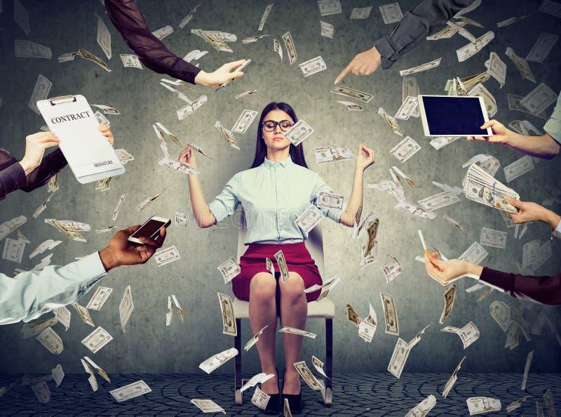 La mujer de negocios está meditando para aliviar la tensión de vida corporativa ocupada debajo de la lluvia del dinero fotos de archivo libres de regalías