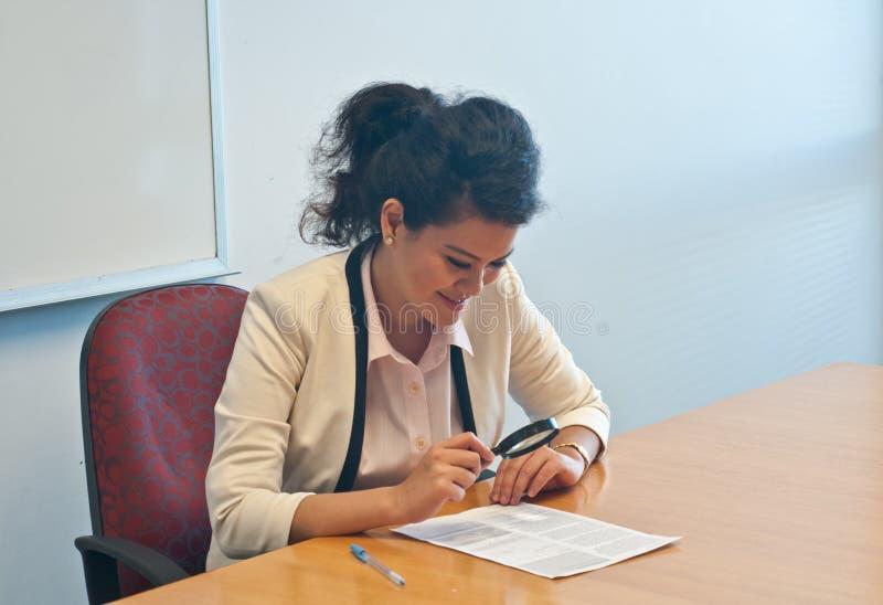 La mujer de negocios examina los detalles del contrato por la lupa imágenes de archivo libres de regalías
