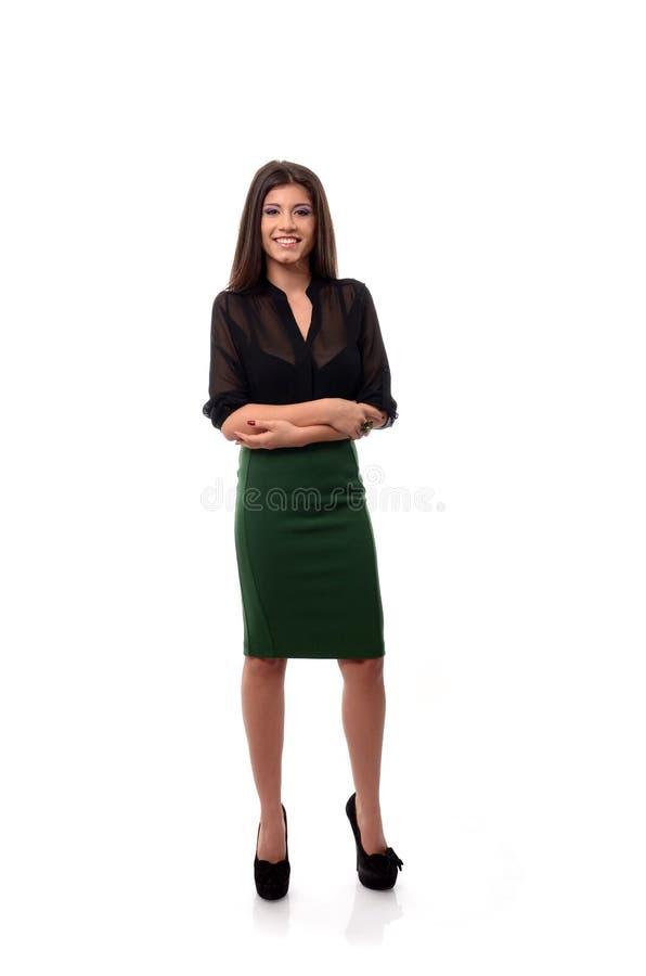 La mujer de negocios feliz con los brazos dobló aislado en blanco foto de archivo