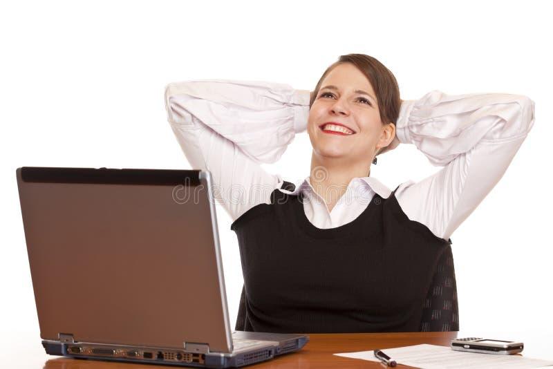 La mujer de negocios feliz joven se relaja en oficina fotografía de archivo