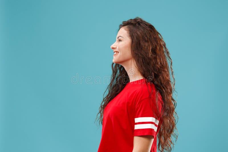La mujer de negocios feliz que se opone y que sonríe contra fondo azul foto de archivo libre de regalías