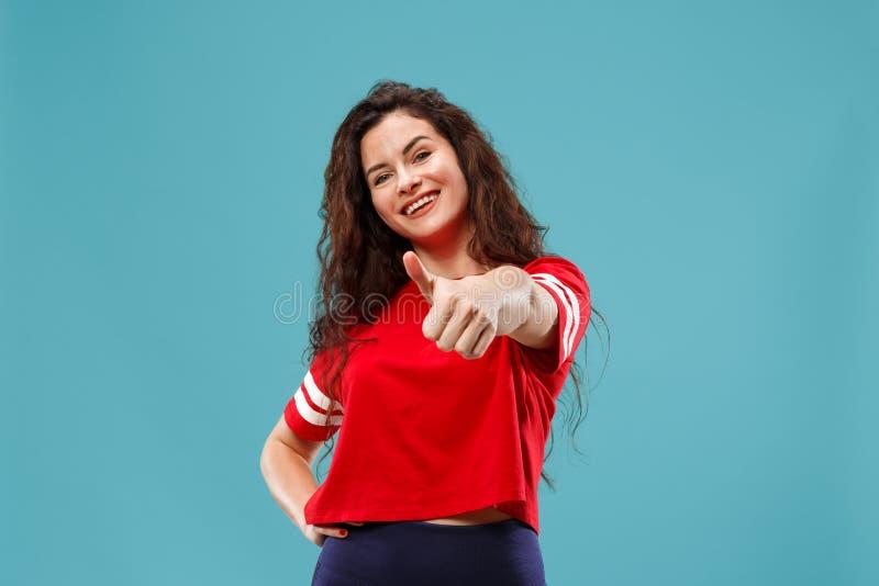 La mujer de negocios feliz que se opone y que sonríe contra fondo azul imagen de archivo libre de regalías