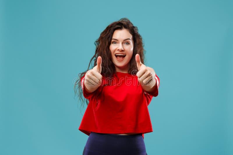 La mujer de negocios feliz que se opone y que sonríe contra fondo azul fotos de archivo