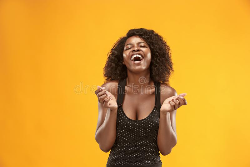La mujer de negocios feliz que se opone y que sonríe contra fondo del oro fotos de archivo libres de regalías