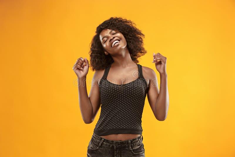 La mujer de negocios feliz que se opone y que sonríe contra fondo del oro fotografía de archivo libre de regalías