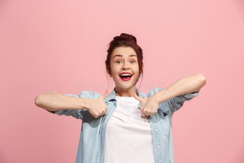 La mujer de negocios feliz que se opone y que sonríe contra fondo rosado imagen de archivo