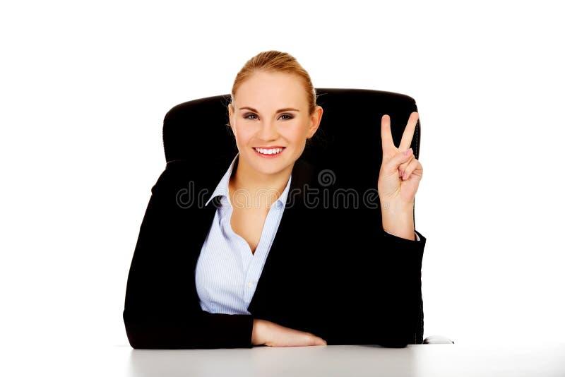 La mujer de negocios feliz que se sienta detrás del escritorio y la victoria de las demostraciones firman imagen de archivo