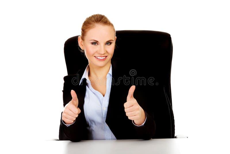 La mujer de negocios feliz que se sienta detrás del escritorio y las demostraciones manosean con los dedos para arriba fotografía de archivo