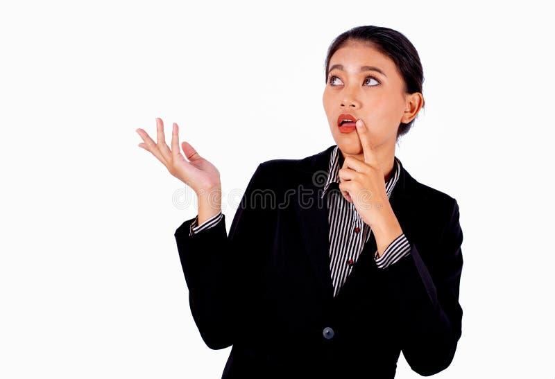 La mujer de negocios hermosa asiática está actuando por actitud encogida en el fondo blanco y también mira a su emoción curiosa d foto de archivo
