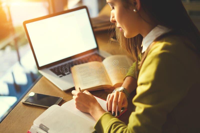 La mujer de negocios hermosa con el pelo oscuro y el suéter amarillo trabaja en coworking imágenes de archivo libres de regalías