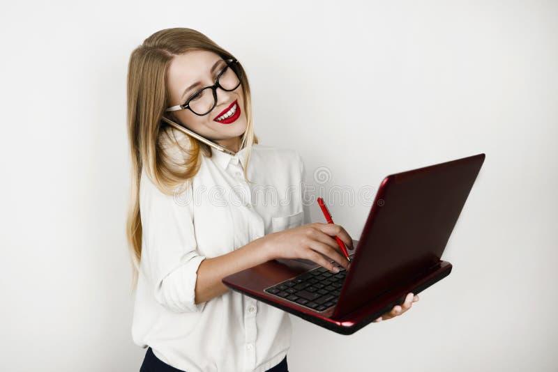 La mujer de negocios hermosa joven en las lentes que trabajaban en el ordenador portátil y que hablaban en smartphone en camino a foto de archivo libre de regalías