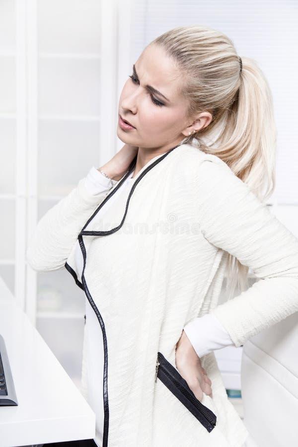 La mujer de negocios hermosa joven tiene dolores en ella detrás imágenes de archivo libres de regalías