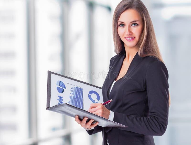 La mujer de negocios joven, atractiva, acertada, estudia las cartas foto de archivo libre de regalías