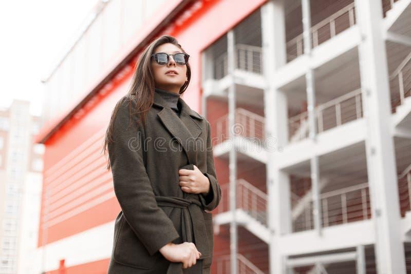 La mujer de negocios joven atractiva elegante con los vidrios de moda en una capa del verde del vintage de la moda camina en la c foto de archivo libre de regalías