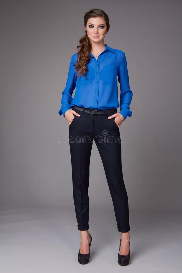 La mujer de negocios joven atractiva hermosa con maquillaje de la tarde se vistió en blusa apretada del pantalones y de seda con  fotografía de archivo