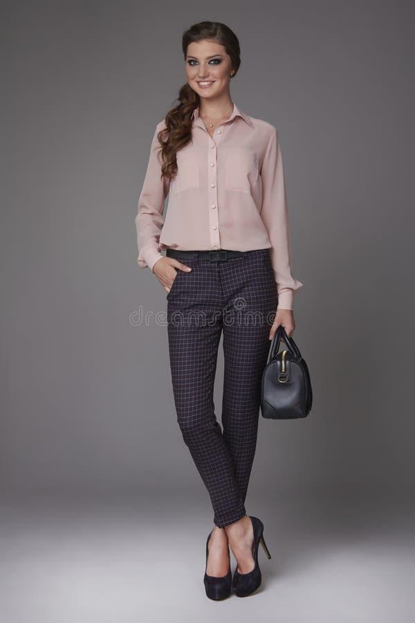 La mujer de negocios joven atractiva hermosa con maquillaje de la tarde se vistió en blusa apretada del pantalones y de seda con  fotos de archivo libres de regalías
