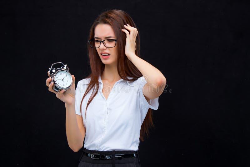 La mujer de negocios joven con el despertador en fondo negro foto de archivo