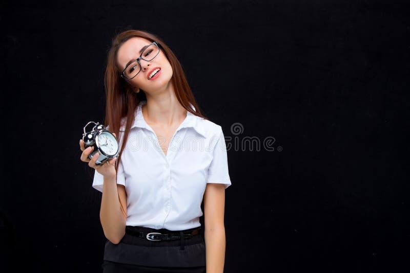 La mujer de negocios joven con el despertador en fondo negro fotografía de archivo libre de regalías