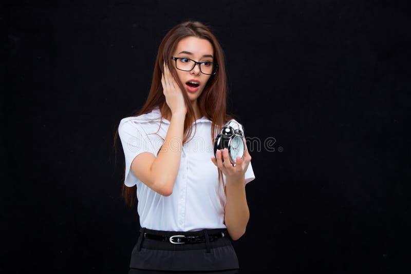 La mujer de negocios joven con el despertador en fondo negro fotos de archivo libres de regalías