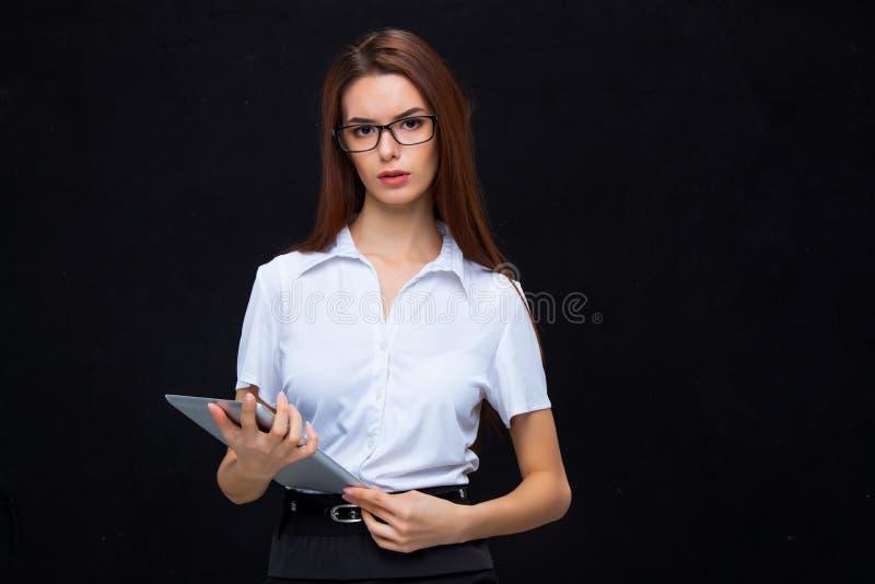 La mujer de negocios joven con la tableta en fondo negro imagen de archivo