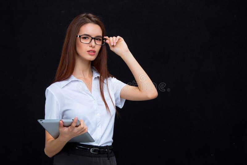 La mujer de negocios joven con la tableta en fondo negro fotografía de archivo