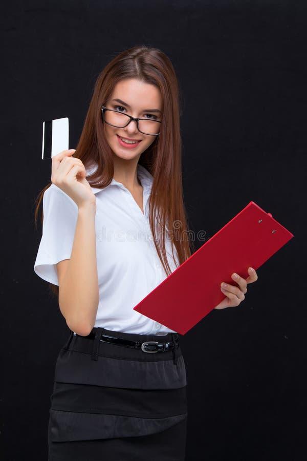 La mujer de negocios joven con la tarjeta de crédito y tableta para las notas sobre fondo gris foto de archivo