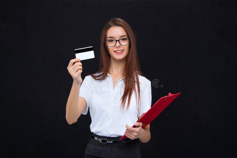 La mujer de negocios joven con la tarjeta de crédito y tableta para las notas sobre fondo gris fotos de archivo libres de regalías