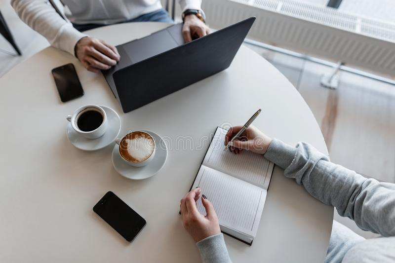 La mujer de negocios joven con un encargado se sienta en un café en una tabla con café con un ordenador portátil y escribe en un  imagen de archivo