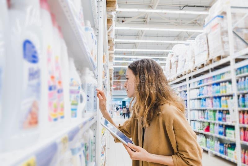 La mujer de negocios joven con una tableta lee la composición de las mercancías en un supermercado fotos de archivo