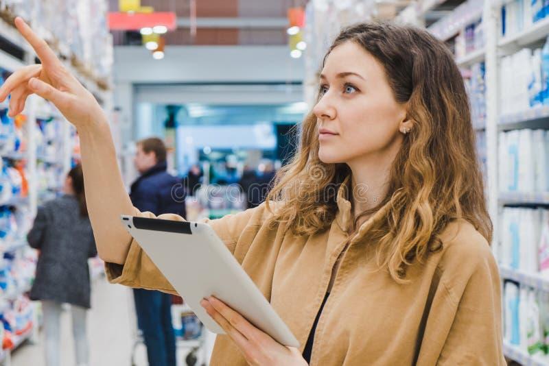La mujer de negocios joven con una tableta señala a las mercancías en un supermercado fotografía de archivo libre de regalías