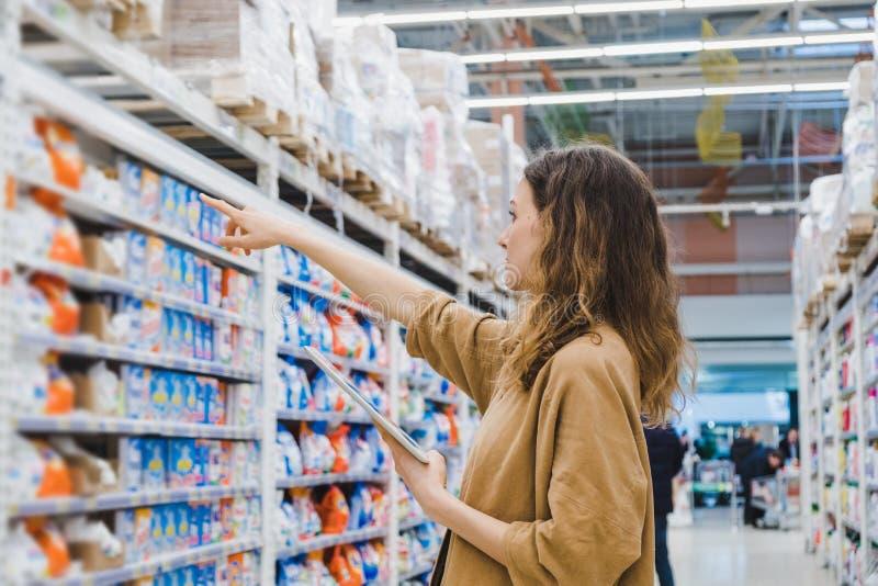 La mujer de negocios joven con una tableta selecciona las sustancias químicas de hogar en un supermercado fotos de archivo